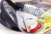 Utensils soaking in kitchen sink