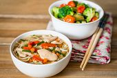 Bowls of Asian soup noodles and vegetables with Chopstick