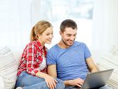 home, technology and relationships concept - smiling couple with laptop computer at home