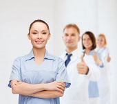 healthcare and medicine concept - smiling female doctor or nurse with team on the back showing thumb