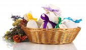 Textile sachet pouches with dried flowers, herbs  and berries  in wicker basket, isolated on white
