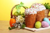 Beautiful Easter cakes, colorful eggs in basket and candles on wooden table on yellow background