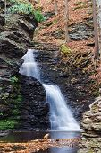 Autumn Waterfall in mountain with rocks and foliage. Bridle Vaill falls  from Bushkill Falls, Pennsy