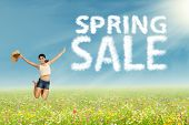 stock photo of filipino  - Excited woman jumping on the park with cloud design of spring sale sign - JPG