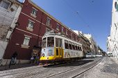 Lisbon, Portugal - September 15, 2013: The iconic number 28 Tram line with an old Lisbon Tram crossi