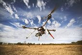 stock photo of helicopter  - Flying drone is filming video in the blue sky - JPG