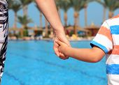 stock photo of responsibility  - Mother and child holding hands on vacation looking at swimming pool concept for family vacations - JPG