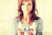 Beautiful young woman holding euros bills and house model - real estate loan concept