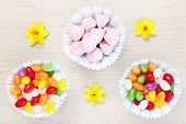 A picture of an Easter composition of sweets and flowers over natural background