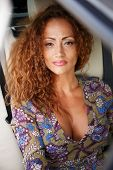 Beautiful middle-aged redhead woman in a luxury car interior