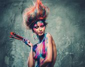 stock photo of muse  - Young woman muse with creative body art and hairdo holding paint brushes - JPG