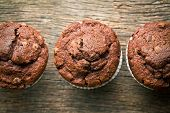 stock photo of chocolate muffin  - top view of chocolate muffins on old wooden background - JPG