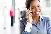 cheerful afro american businesswoman talking on cell phone