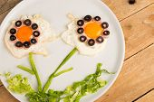stock photo of olive shaped  - Sunny side up eggs decorated with vegetables kid food - JPG
