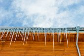 Roof Of The House With Hanging Icicles On Blue Sky Background