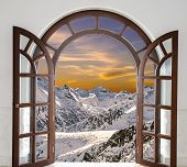 Arch Door Opened With Views Of The Peaks Of Snowy Mountains And Sunset