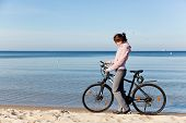 Young woman tracking her route on the smartphone gps during the bicycle trip on the beach. Sea in th