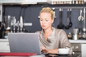 stock photo of nightgown  - Business woman in her nightgown working from her dining table in the morning - JPG