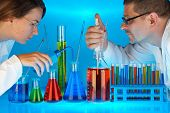 stock photo of chemical reaction  - two laboratory technicians with many different coloured chemical solutions in laboratory glasses with pipettes on blue background - JPG