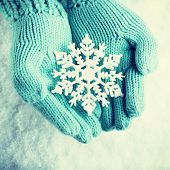 stock photo of knitting  - Woman hands in light teal knitted mittens are holding a beautiful snowflake in a snow background - JPG