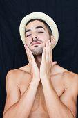 foto of half-naked  - Handsome man half naked with hat smiling on black backgound - JPG