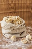 image of lien  - Russian pelmeni on a lien bag on a wooden background - JPG