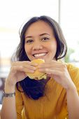 stock photo of starving  - Pretty Young Woman Eating Burger Enjoying Break Lunch In Cafe - JPG
