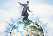 picture of unicycle  - Man riding unicycle around the globe with major cities concept - JPG