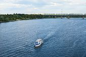 stock photo of sloop  - The boat floating in the blue Dnieper waters against the summer Kyiv landscape - JPG