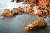 foto of rough-water  - Beautiful stones in sea water at sunset taken at slower shutter speed - JPG