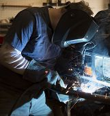 stock photo of welding  - Man wearing welding helmet and welding the bumper of a vehicle - JPG