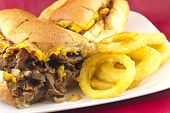 image of cheesesteak  - A messy Philly Cheesesteak with onions peppers and mushrooms onion rings on the side