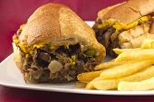 picture of cheesesteak  - A messy Philly Cheesesteak with onions peppers and mushrooms fries on the side - JPG