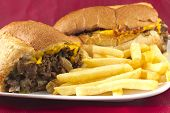 pic of cheesesteak  - A messy Philly Cheesesteak with onions peppers and mushrooms fries on the side - JPG