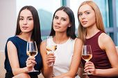 stock photo of evening gown  - Three beautiful young women in evening gown sitting on the couch and holding glasses with wine - JPG