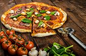 image of salami  - Rustic pizza with salami mozzarella and spinach on a clay plate - JPG