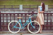 stock photo of beauty  - Young beautiful elegantly dressed woman with bicycle. Beauty fashion and lifestyle