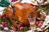 picture of christmas dinner  - Garnished roasted turkey on Christmas decorated table with candles and flutes of champagne - JPG