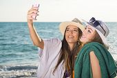 picture of memento  - Pretty Young Girls at the Beach Taking Selfie Happily on a Sunny Climate - JPG