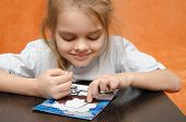 picture of applique  - five year old girl sitting at the table and collects sand applique - JPG