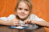 stock photo of applique  - five year old girl sitting at the table and collects sand applique - JPG