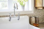 stock photo of sink  - Rustic white porcelain kitchen sink with curved faucet and tile backsplash under large window - JPG