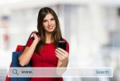 image of internet shop  - Young woman holding shopping bags and a mobile phone - JPG