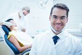 image of foreground  - Portrait of smiling male dentist with assistant examining womans teeth in the dentists chair - JPG