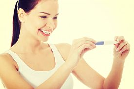 stock photo of teen pregnancy  - Happy smiling woman with positive pregnancy test - JPG