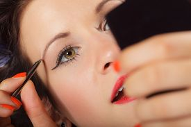 pic of eyebrows  - Closeup part of face woman plucking eyebrows depilating with tweezers - JPG