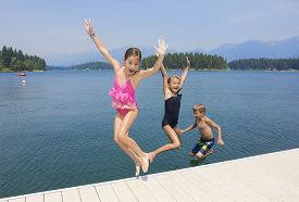 stock photo of dock a lake  - Kids playing at the lake on their summer vacation  - JPG
