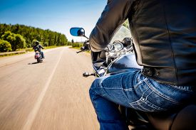 stock photo of biker  - Bikers driving a motorcycle rides along the asphalt road  - JPG