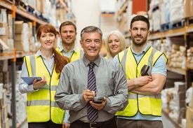 stock photo of warehouse  - Smiling warehouse team with arms crossed in a large warehouse - JPG