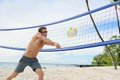 stock photo of passed out  - Beach volleyball man playing forearm pass hitting volley ball during game on summer beach - JPG